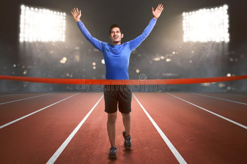 跑到终点线的愉快的亚裔运动员人