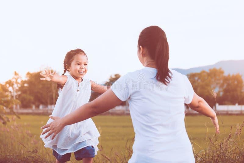 跑到他们的母亲的愉快的亚裔小孩女孩 库存图片