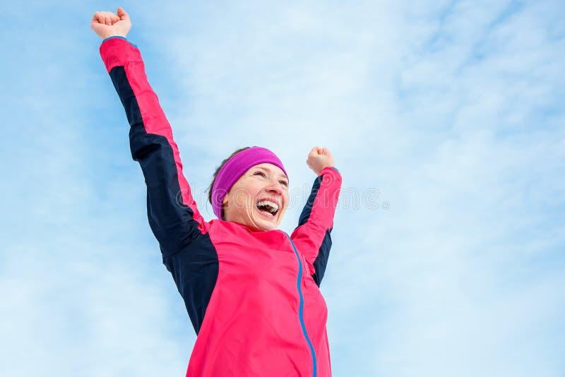 跑和体育成功 庆祝胜利和培养的愉快的妇女他的手  母赛跑者成功反对蓝天 库存照片
