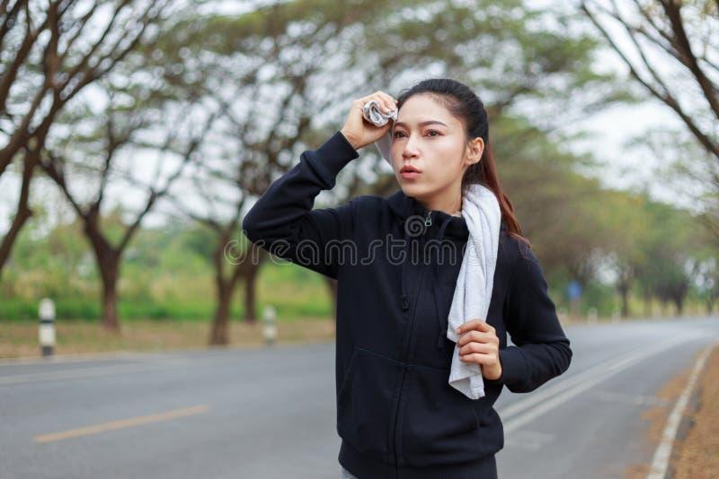 跑和抹她的汗水的年轻运动的妇女与毛巾 库存照片