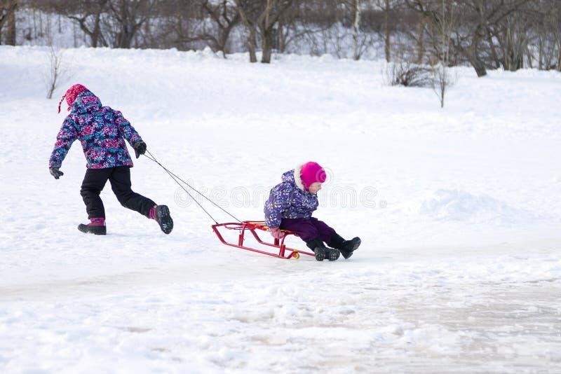 跑和拉扯她的一个雪撬的更老的女孩年轻姐妹在冰在多雪的冬天公园 免版税库存照片