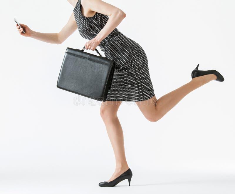 跑和拿着她的手机a的无法认出的女实业家 图库摄影