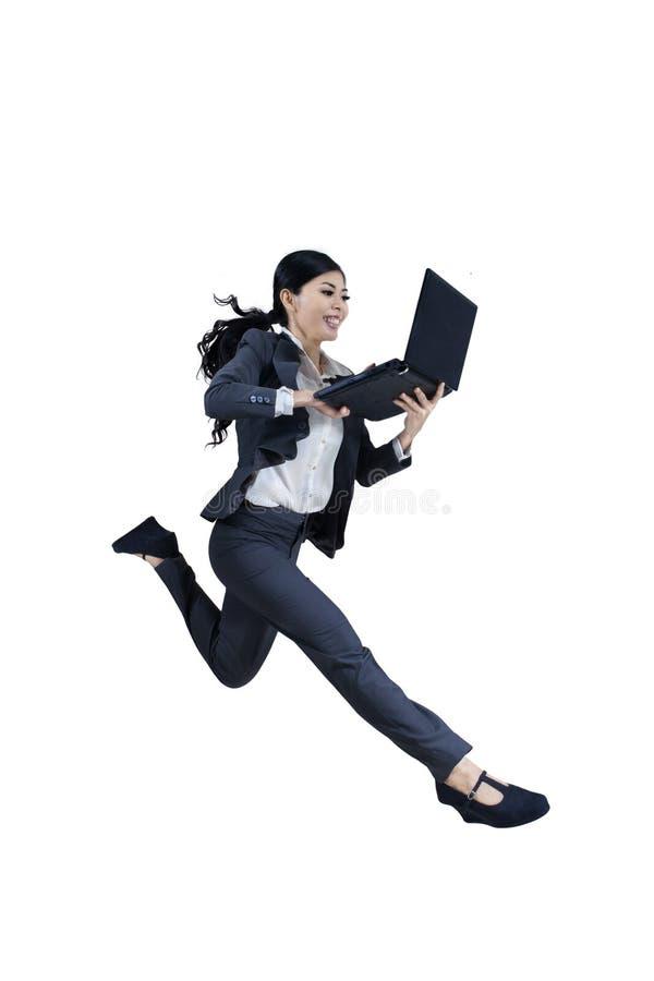 跑和拿着膝上型计算机的激动的妇女 库存照片