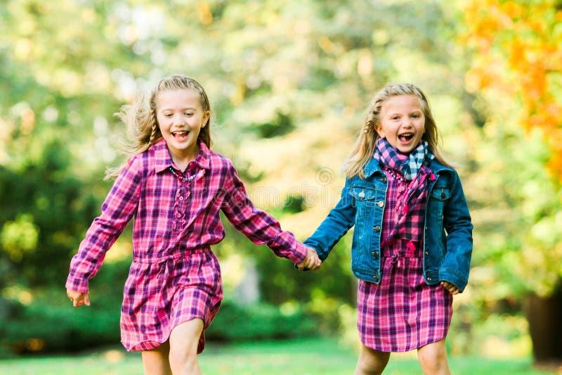跑和握手的两个年轻白种人姐妹 免版税图库摄影