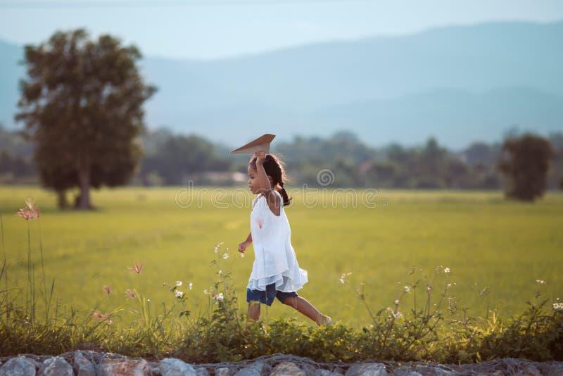 跑和演奏玩具纸飞机的逗人喜爱的亚裔儿童女孩 免版税图库摄影