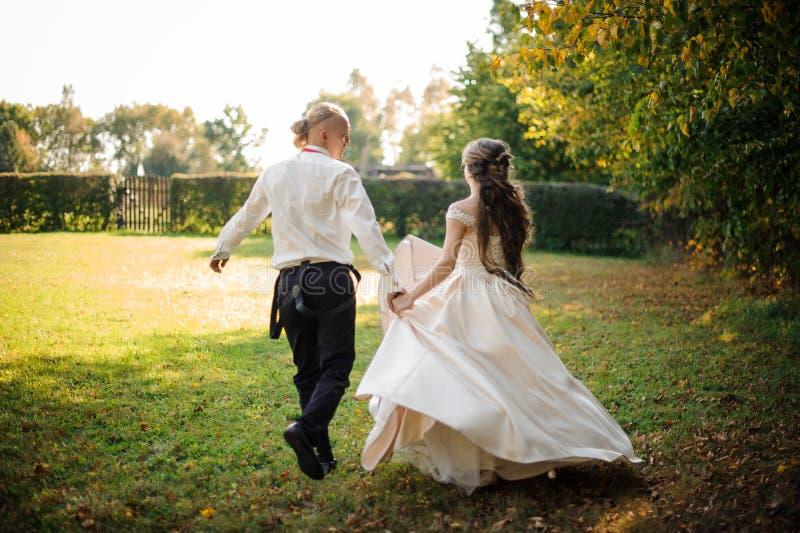 跑和笑横跨公园的愉快的已婚夫妇后面看法  免版税库存照片