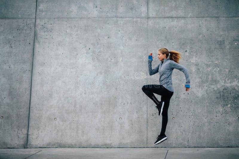 跑和跳跃在城市街道上的少妇 免版税库存照片