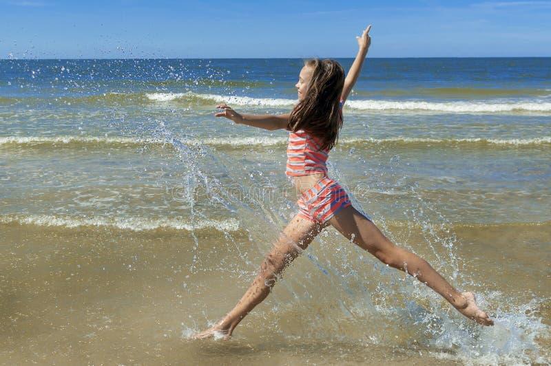 跑和跳跃在海滩的美女 库存照片