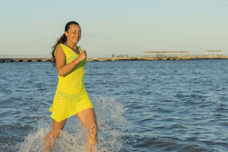 跑和飞溅在水中的妇女在海滩 运行海水妇女年轻人 秀丽少女在假日 以黄色 图库摄影