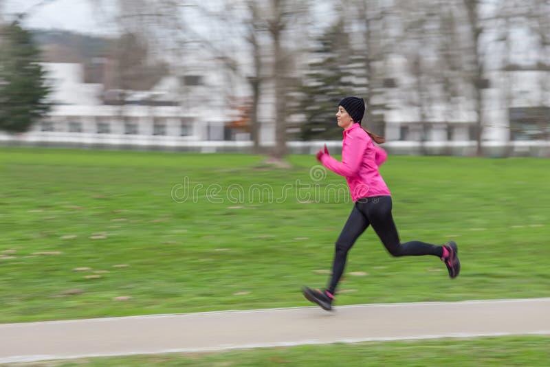 跑在一个冷的冬日的少妇 免版税库存照片