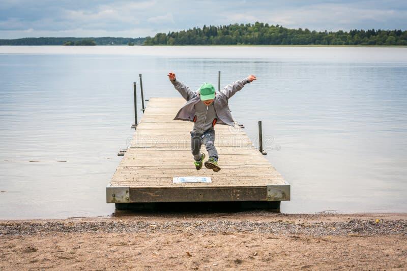 跑在一只跳船和跃迁的一个年轻男孩的正面图在空气往海滩 免版税图库摄影