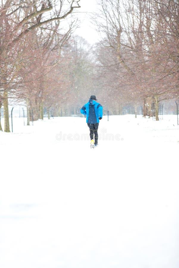 跑在一多雪的天的人 免版税库存照片