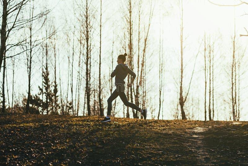 跑在一条农村路的运动的女孩 免版税图库摄影