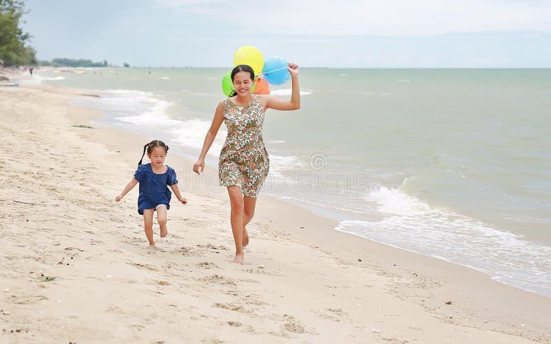 跑在与五颜六色的气球的海滩的母亲和女儿画象在母亲手上 E 免版税图库摄影