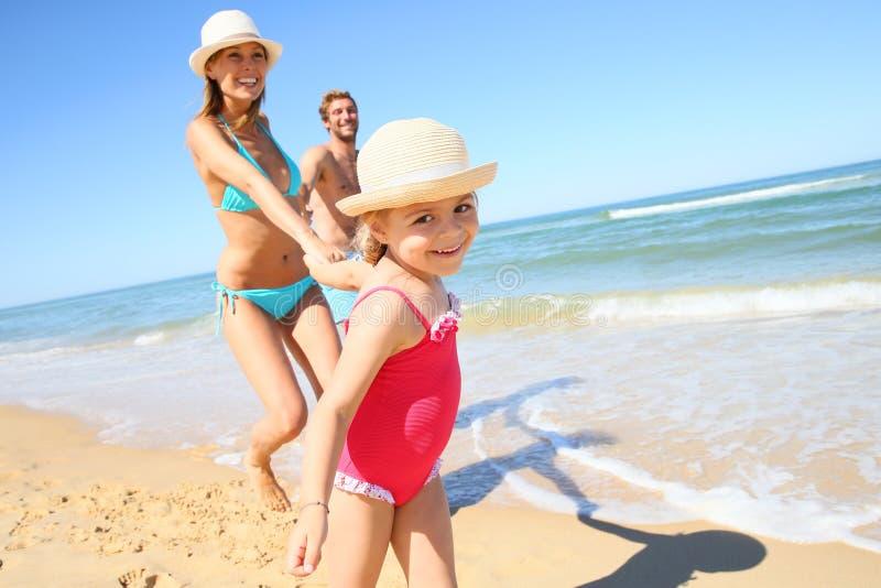 跑在与父母的海滩的小女孩画象 图库摄影