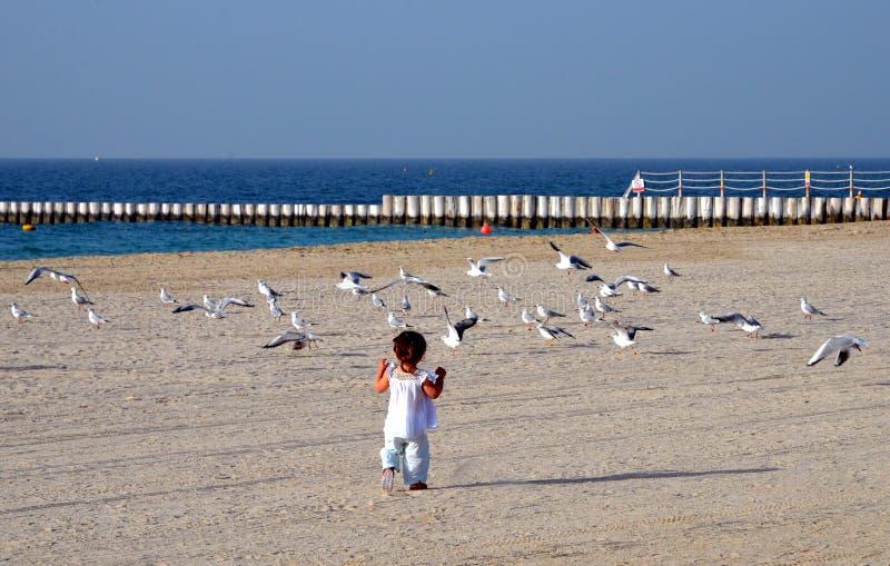 跑在与白色沙子的海滩的一个愉快的女婴在迪拜,阿拉伯联合酋长国 免版税库存图片