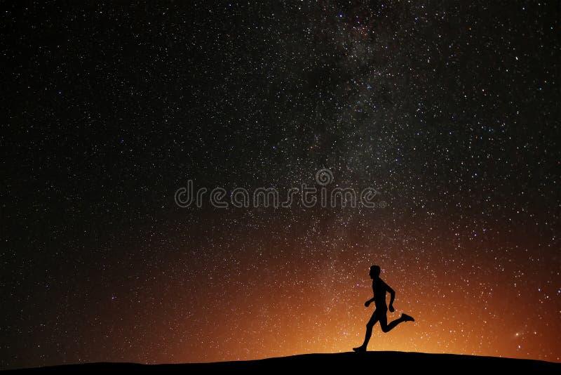 跑在与美丽的星的小山的赛跑者运动员 免版税库存图片