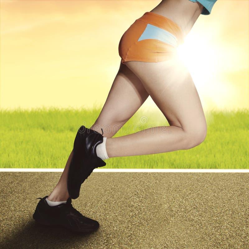 跑在与肌肉腿的日出的妇女 免版税库存图片