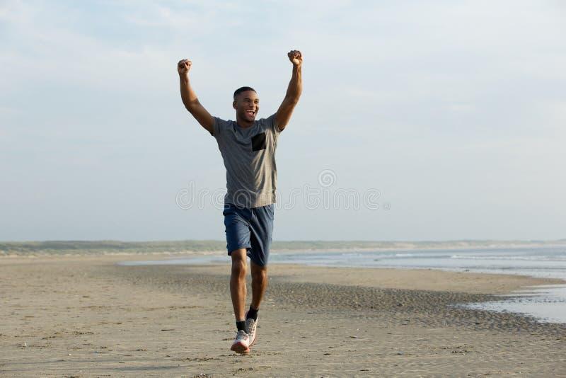 跑在与被伸出的胳膊的海滩的人 库存照片