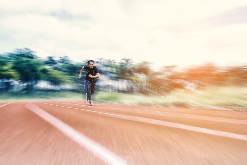 跑在与辐形迷离,体育和活动概念的轨道的连续人 免版税图库摄影