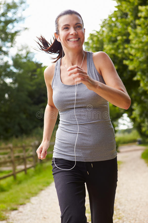 跑在乡下佩带的耳机的妇女 免版税库存图片