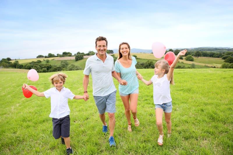 跑在乡下的快乐的四口之家 库存图片