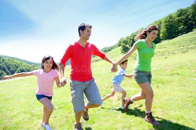 跑在乡下的愉快的家庭 免版税库存图片