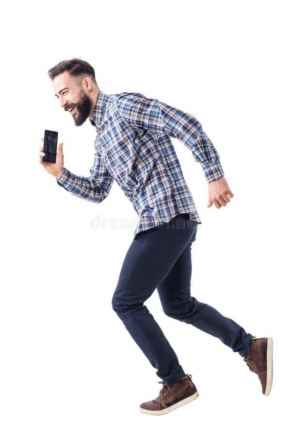 跑在仓促的笑的愉快的有胡子的商人谈话在手机 图库摄影