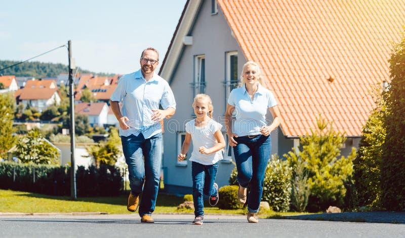 跑在他们新的家前面的幸福家庭 图库摄影
