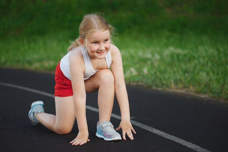跑在体育场的愉快的女孩 免版税库存图片