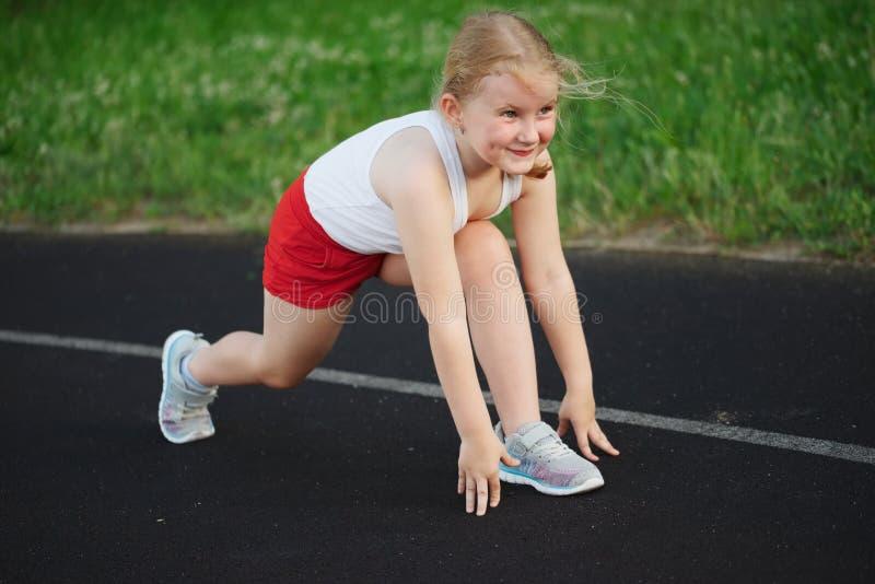 跑在体育场的愉快的女孩 库存图片
