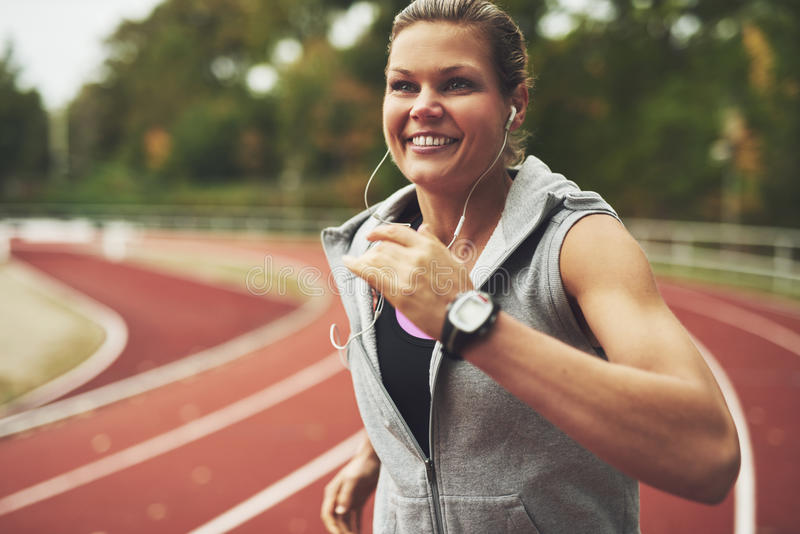 跑在体育场的年轻微笑的妇女 库存照片