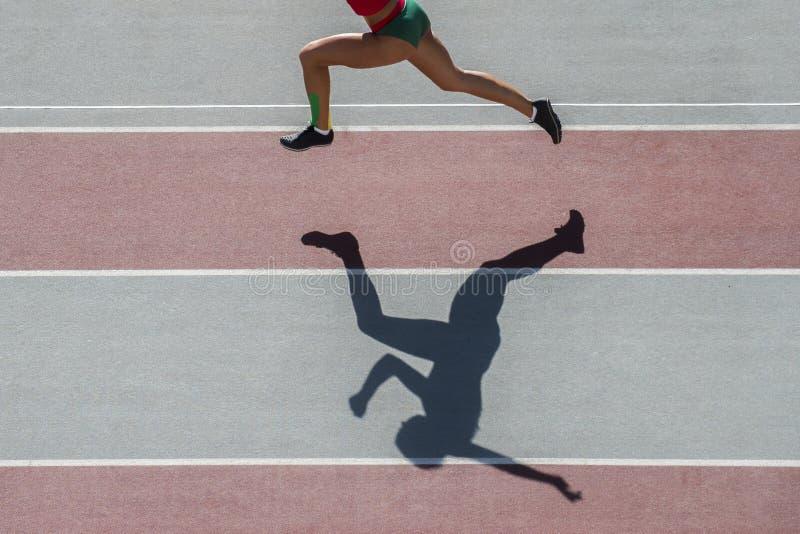 跑在体育场背景的剪影的一位白种人妇女赛跑者慢跑者 免版税库存图片