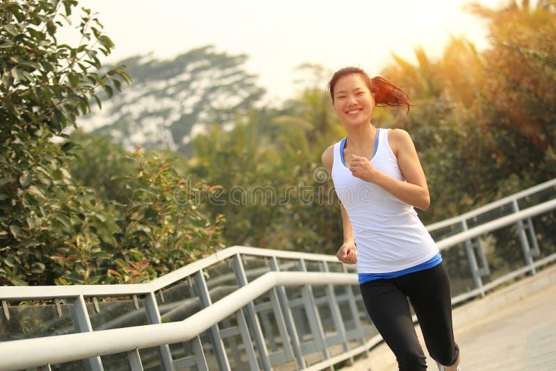 跑在公园人行桥的亚裔妇女 图库摄影