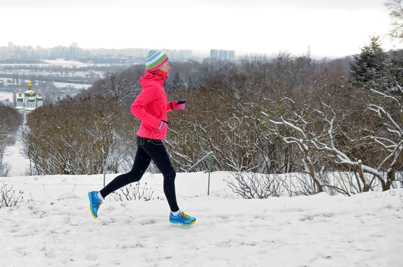 跑在公园的冬天:跑步在雪的愉快的活跃妇女赛跑者有Kyiv市地平线视图、户外运动和健身 免版税库存图片