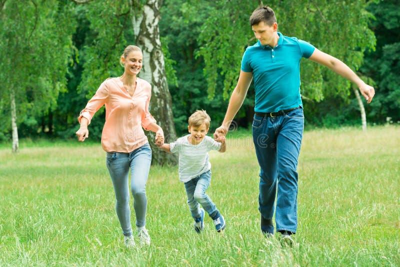 跑在公园的家庭 库存照片