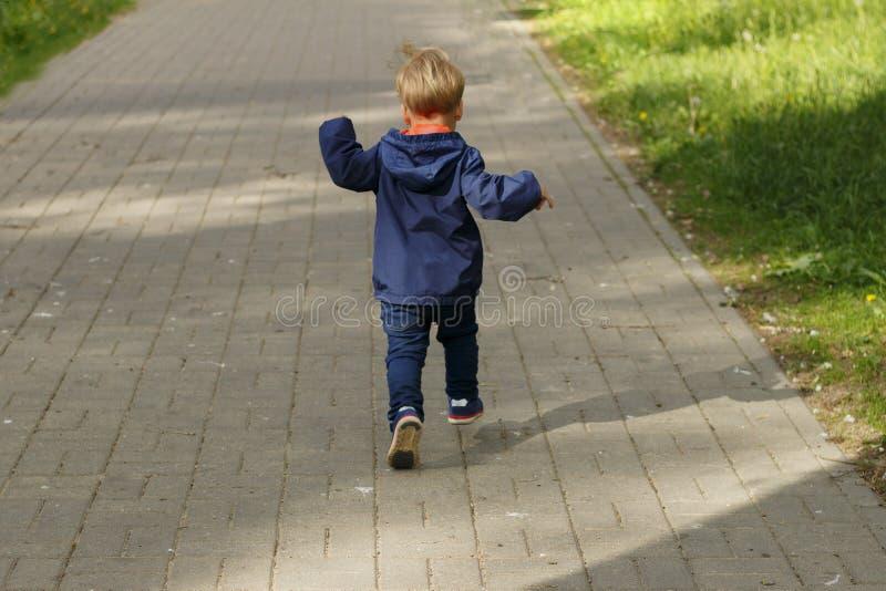 跑在公园的小男孩 后面观点的步行的小孩在公园 免版税图库摄影