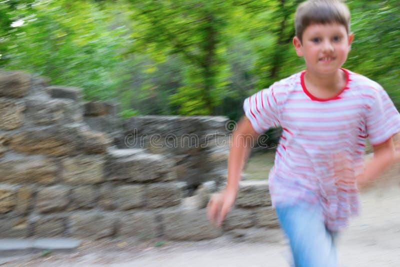 跑在公园的快乐的男孩 免版税库存图片