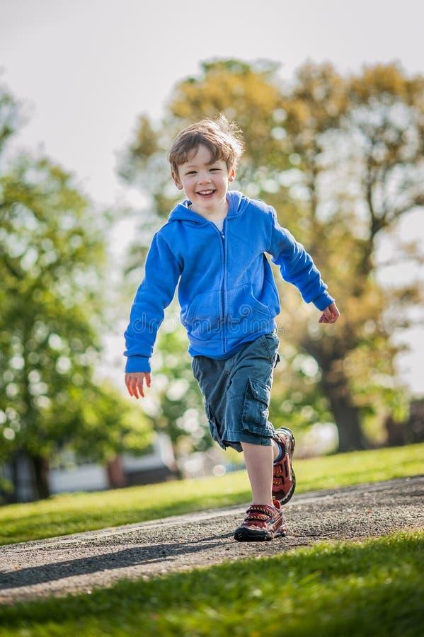 跑在公园的愉快的男孩 库存照片