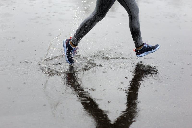 跑在公园的赛跑者妇女在雨中 m的跑步的训练 免版税库存图片