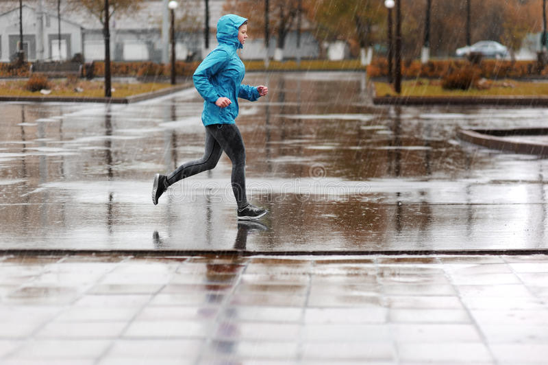 跑在公园的赛跑者妇女在雨中 m的跑步的训练 库存图片