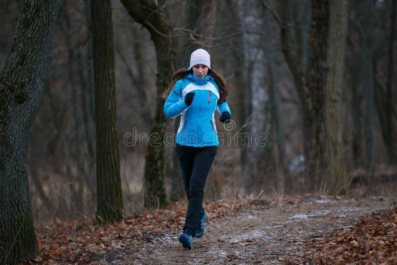 跑在冬天公园的足迹的少妇 免版税库存照片