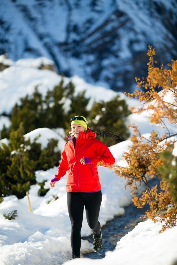 跑在冬天山的妇女足迹 免版税库存照片