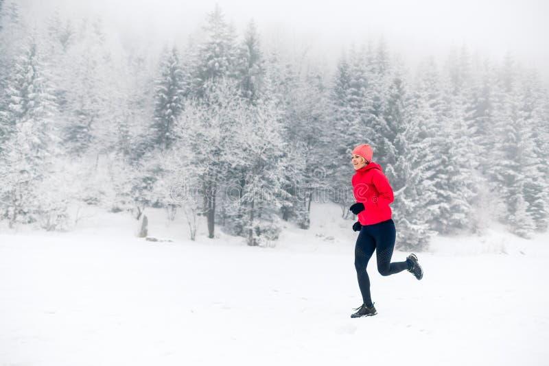 跑在冬天山的雪的女孩 体育、健身启发和刺激  库存图片