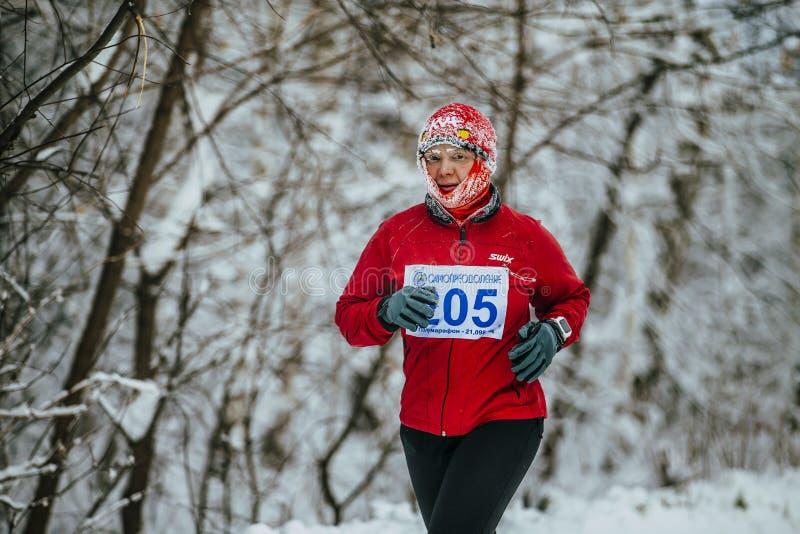 跑在冬天积雪的胡同的中年女子运动员在公园 库存图片