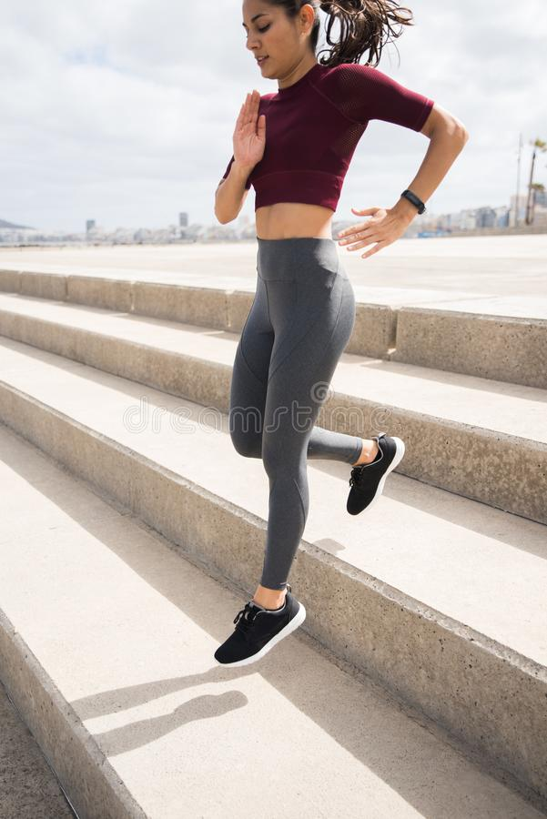跑在台阶下的可爱的运动的妇女 免版税库存图片