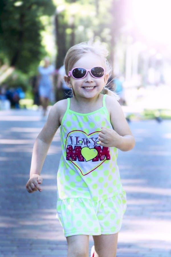 跑在城市公园的愉快的女孩在夏日 正面幼稚emitions 库存照片