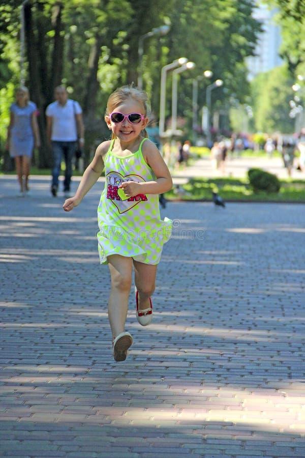 跑在城市公园的愉快的小女孩 正面幼稚emitions 跑沿道路的孩子微笑和高兴 愉快 库存照片