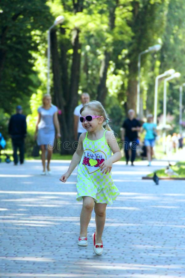 跑在城市公园的愉快的小女孩 正面幼稚emitions 库存图片