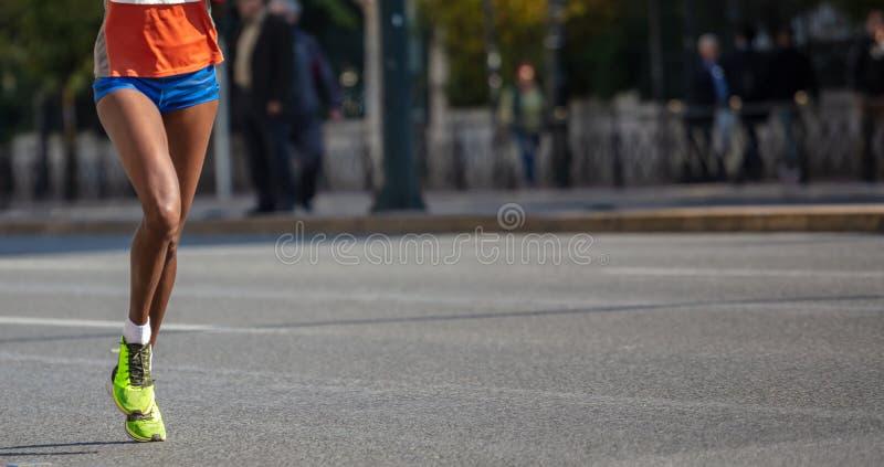 跑在城市道路 年轻女人赛跑者,正面图,横幅,迷离背景 免版税库存图片